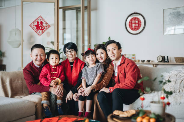 three generations of joyful asian family embracing and celebrating chinese new year together - chinese new year stock pictures, royalty-free photos & images