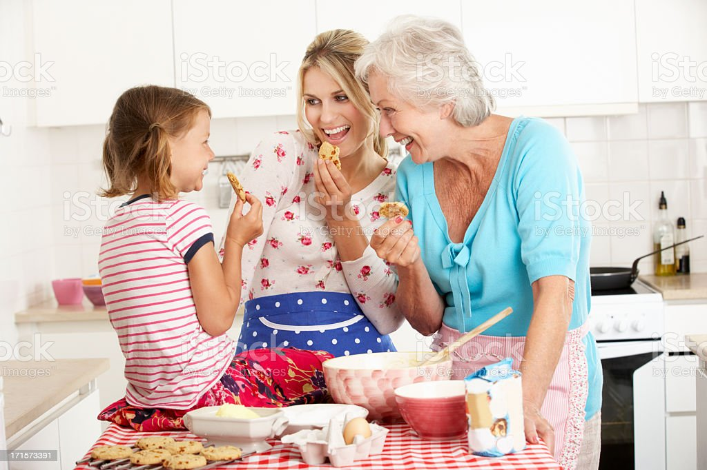 Three generations of women baking cookies together royalty-free stock photo