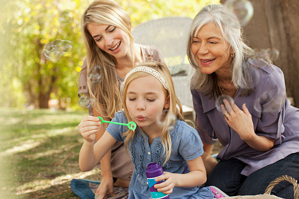 Three generations of women blowing bubbles stock photo