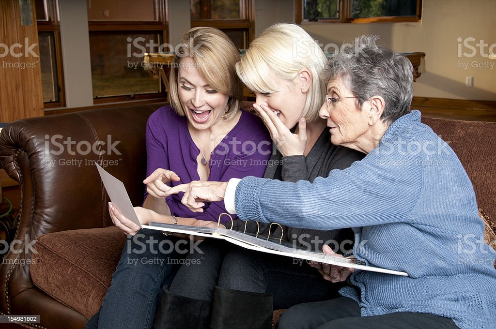 Three Generations of Women Look Through Photo Album stock photo