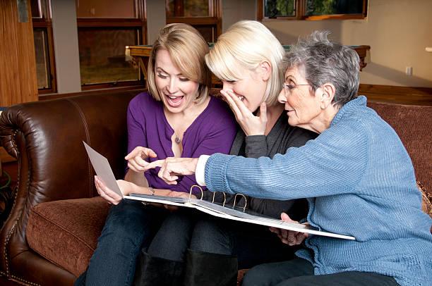 Three Generations of Women Look Through Photo Album stock photo