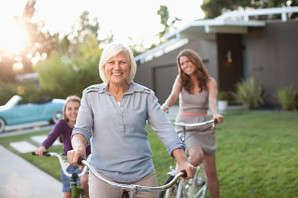 three generations of women riding bicycles - vrouw 60 stockfoto's en -beelden