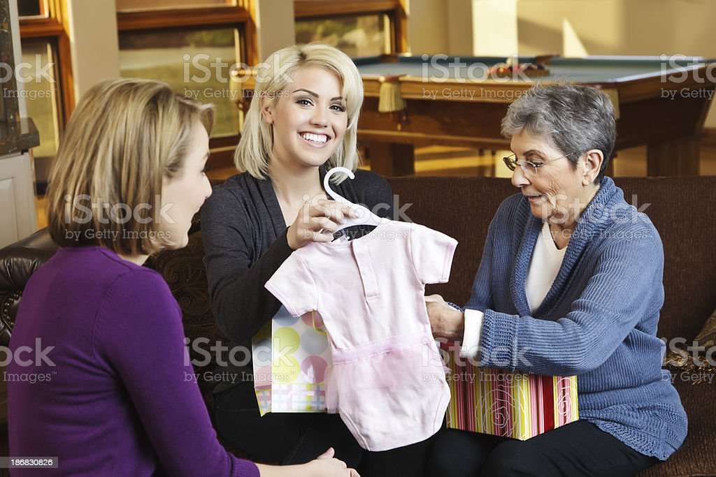 Three generations of women celebrating with gifts for impending baby.