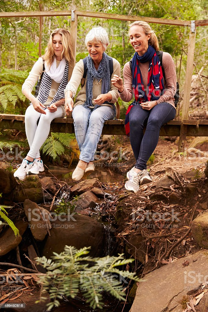 Three generations of women sitting on a bridge in forest stock photo