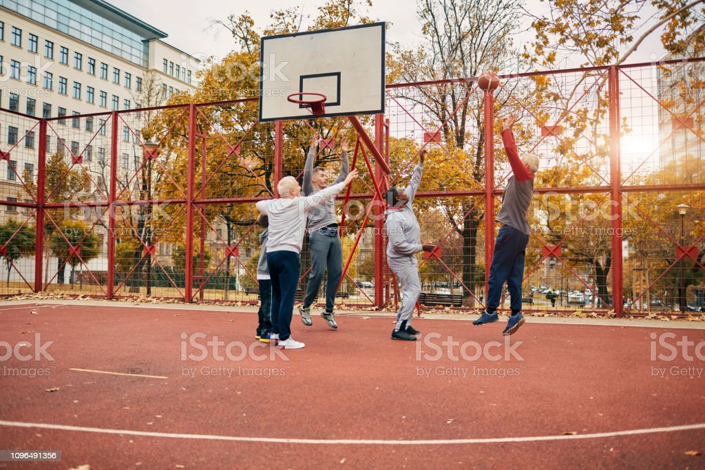 Boy playing basketball with father, grandfather and grandfather\'s...