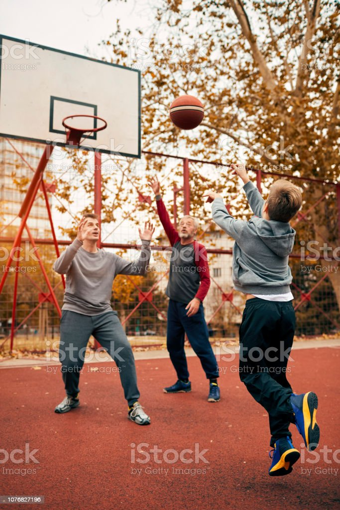 Boy playing basketball with father and grandfather in public park.