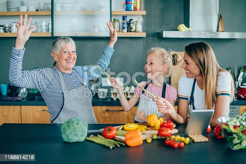 638984280 istock photo Three generations women laughing in the kitchen 1168614218