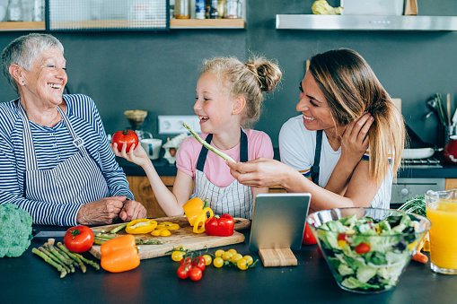 638984280 istock photo Three generations women laughing in the kitchen 1180551819