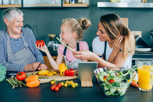 638984280 istock photo Three generations women laughing in the kitchen 1202694763
