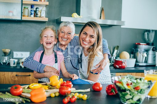 638984280 istock photo Three generations women laughing in the kitchen 1205957814