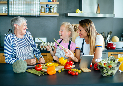 638984280 istock photo Three generations women laughing in the kitchen 1207327927