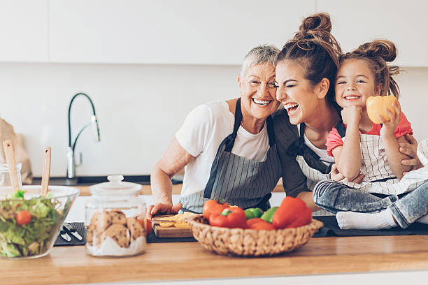 three generations women laughing in the kitchen - kids cooking stock photos and pictures