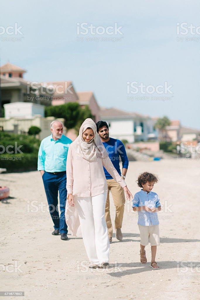 Three Genration Arabic family walking on the beach stock photo