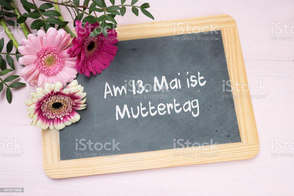 Three Gerbera Flowers On A Writing Chalkboard German Text Am