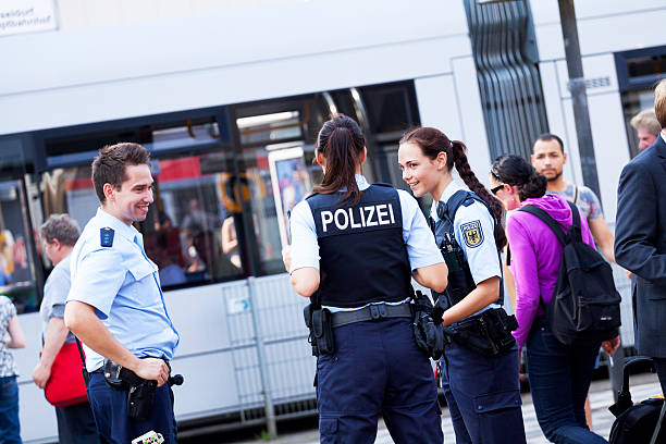 Three german policemen Düsseldorf, Germany - July 22, 2014: Capture of three german policemen. Two are policewomen. Women are wearing bulletproof vest. Policemen are talking. In background is tram. At left are people. north rhine westphalia stock pictures, royalty-free photos & images