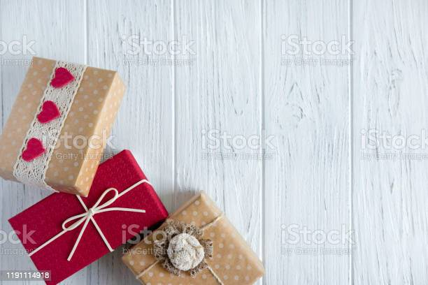 Three gifts close up on a light wooden background with a place for picture id1191114918?b=1&k=6&m=1191114918&s=612x612&h=ahlfeub1dbica8mbfijk3x3omxurja2p1lxl 94ilwq=