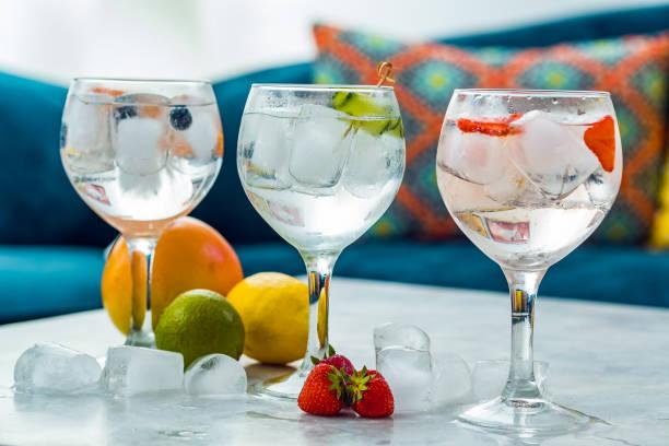 drie gin tonic cocktails met aardbeien, limoen en bosbessen. - gin tonic stockfoto's en -beelden