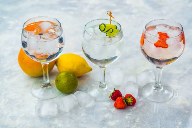 Three gin tonic cocktails with strawberries, lime and blueberries. stock photo