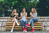 Group of teenage girls sitting on a bench and drinking orange juice, downtown.