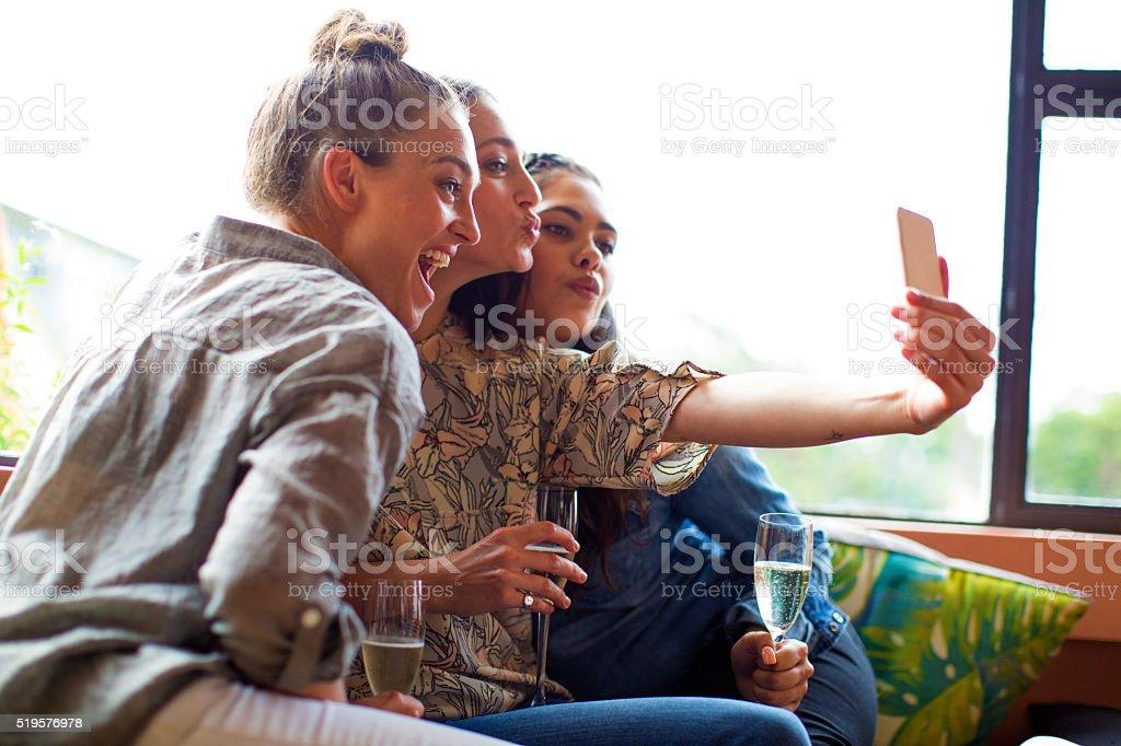Three girlfriends having champagne taking selfie stock photo