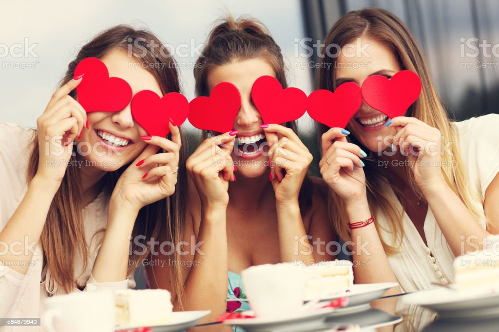 Three girlfriends holding hearts in cafe stock photo