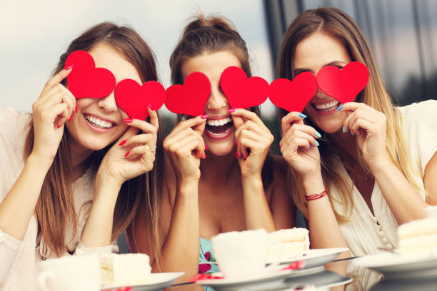 three girlfriends holding hearts in cafe - vaisselle picto photos et images de collection