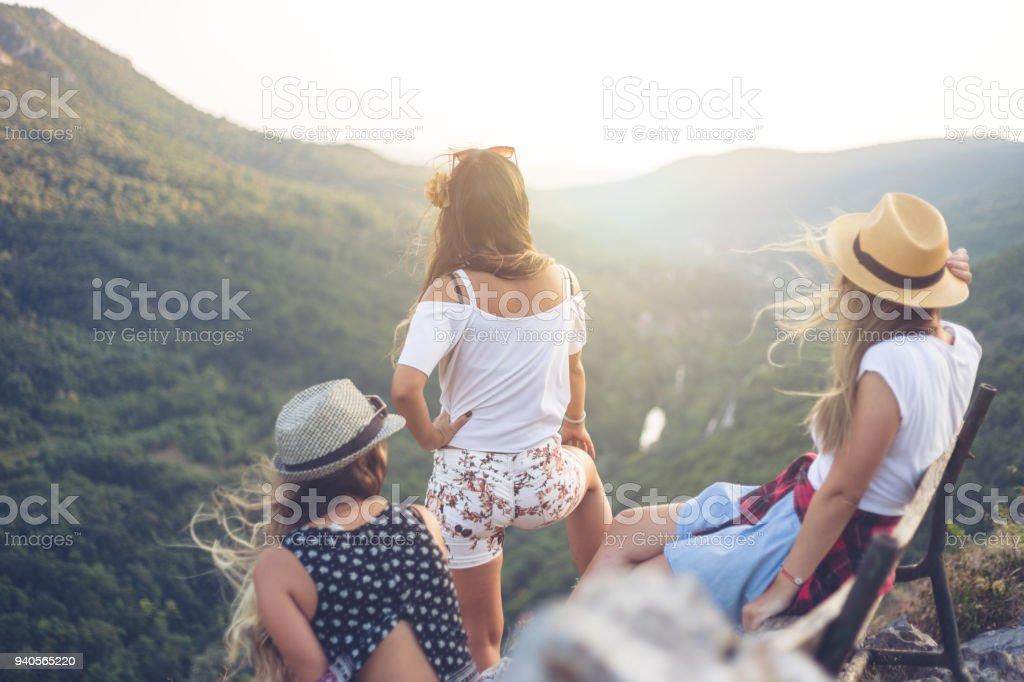 Three girlfriends on mountain peak stock photo