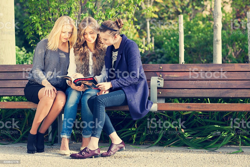 Three girlfriends reading magazine on bench outdoors stock photo