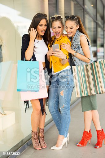 Three fashionable female friends are surprised by the news they have seen on mobile phone.