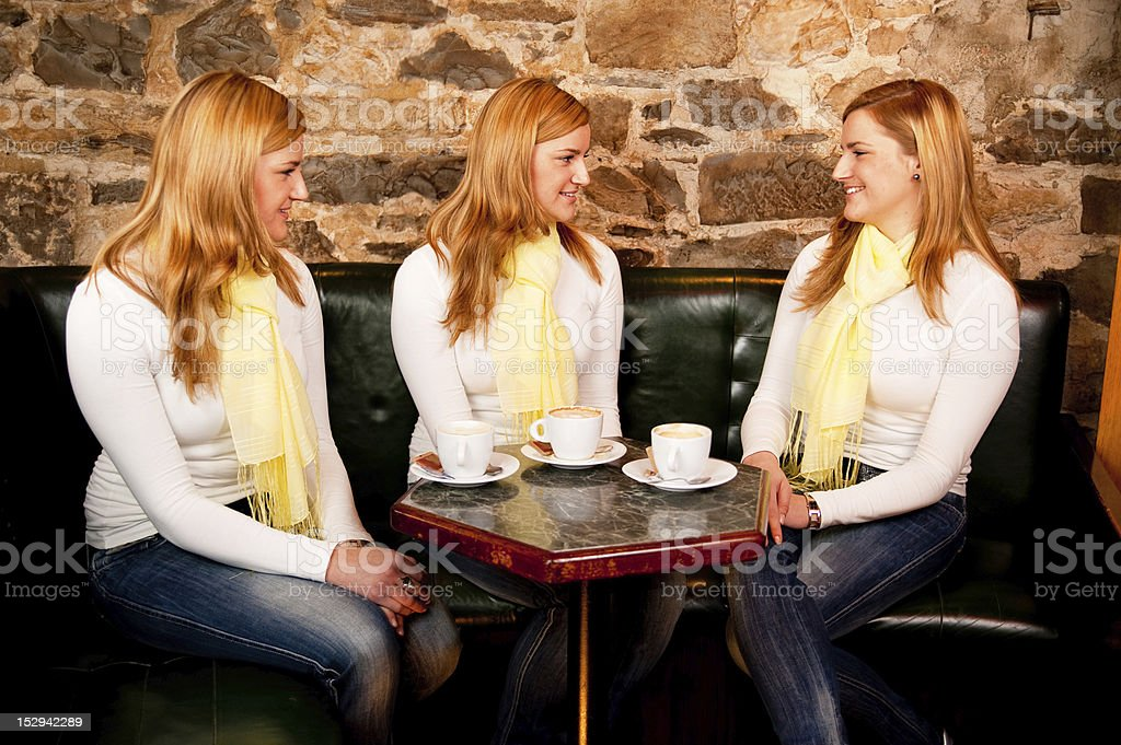 Three girls ahving a conversation in coffee shop royalty-free stock photo
