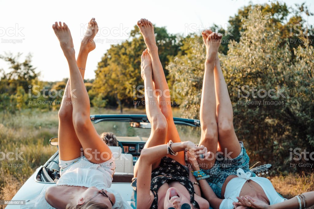 Three girls are lying on the trunk stock photo