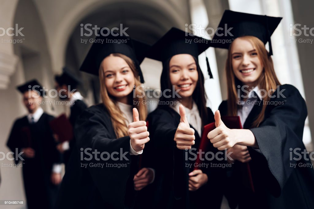 Three girls are posing for a camera at the university. stock photo