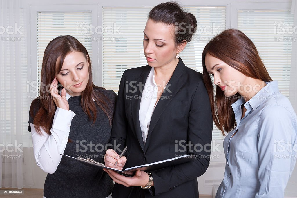 Three girls are studying the information in a folder stock photo