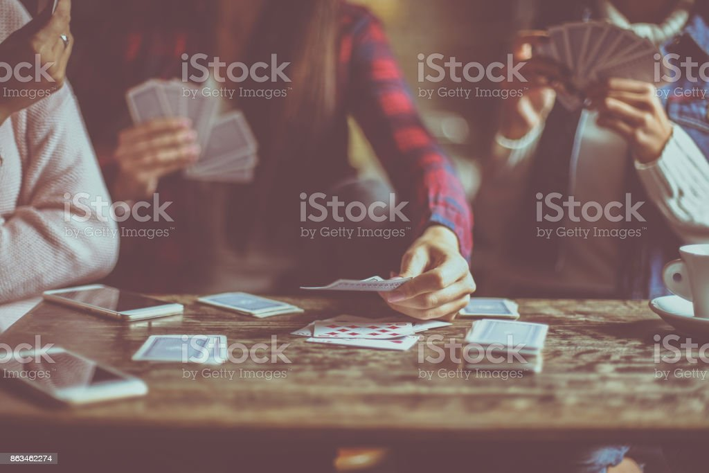 Three girls at home playing cards together. Close up. stock photo