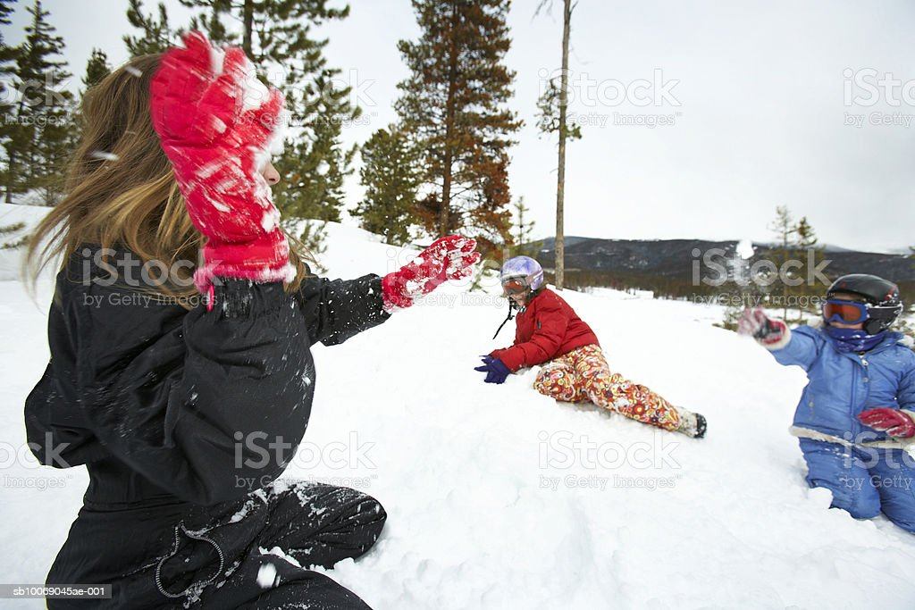 Three girls (8-13) fighting with snowballs royalty-free stock photo