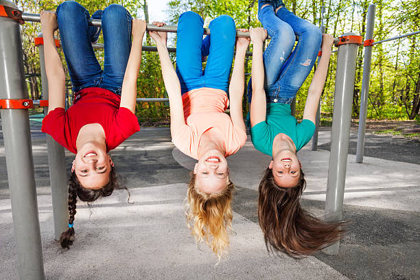 three girls hanging upside-down on brachiating bar - horizontal bar stock photos and pictures