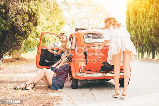 Funny picture of three women with red vintage car