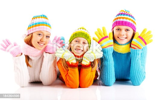 Three beautiful sisters with smiles on their faces are lying on the floor and looking at the camera. They are wearing colorful knit hats and sweaters and they are isolated on white background.