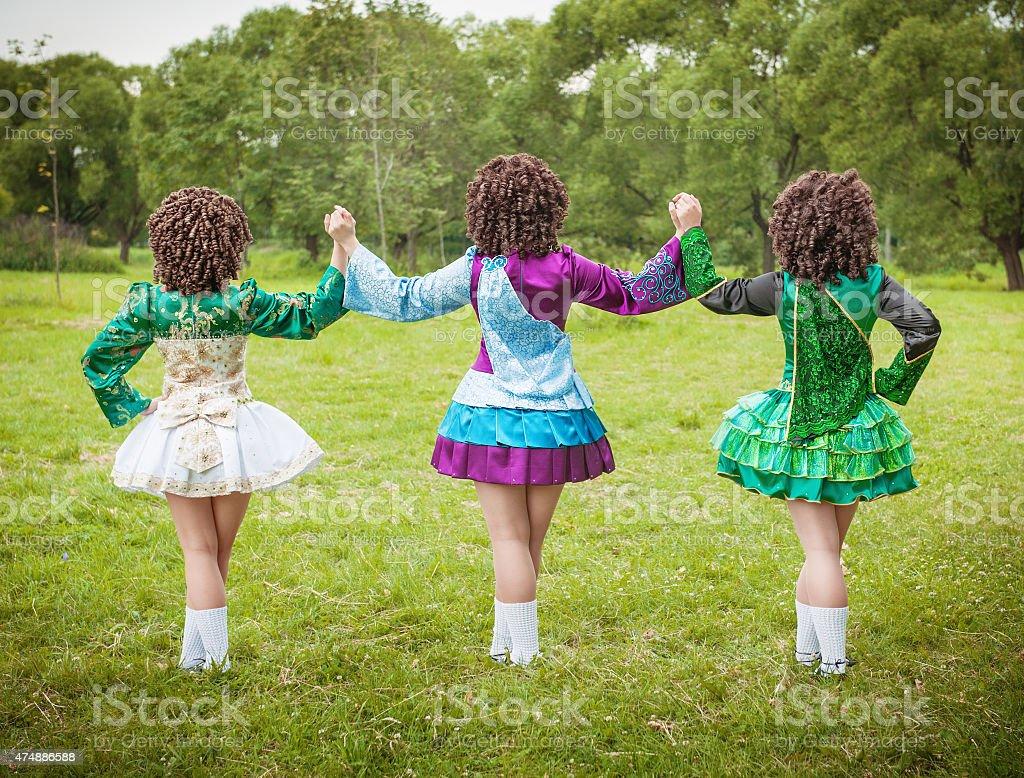 Three girls in irish dance dress and wig posing outdoor stock photo