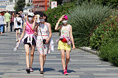 Moscow, Russia - July 2020: Three girls walking on a summer street in Moscow. People in city during covid-19 coronavirus pandemic, hot sunny weather