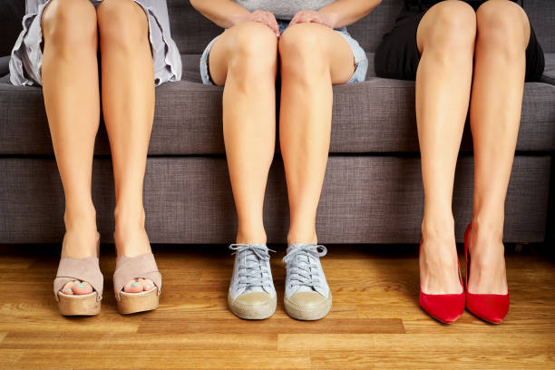 Three girls legs sitting on the couch in different shoes and different styles on couch.