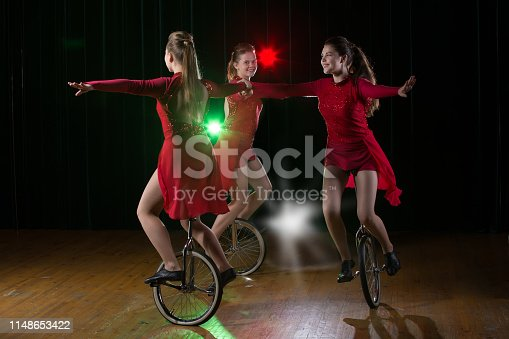 Three girls on a monocycle perform on stage. Circus Artists on Bikes