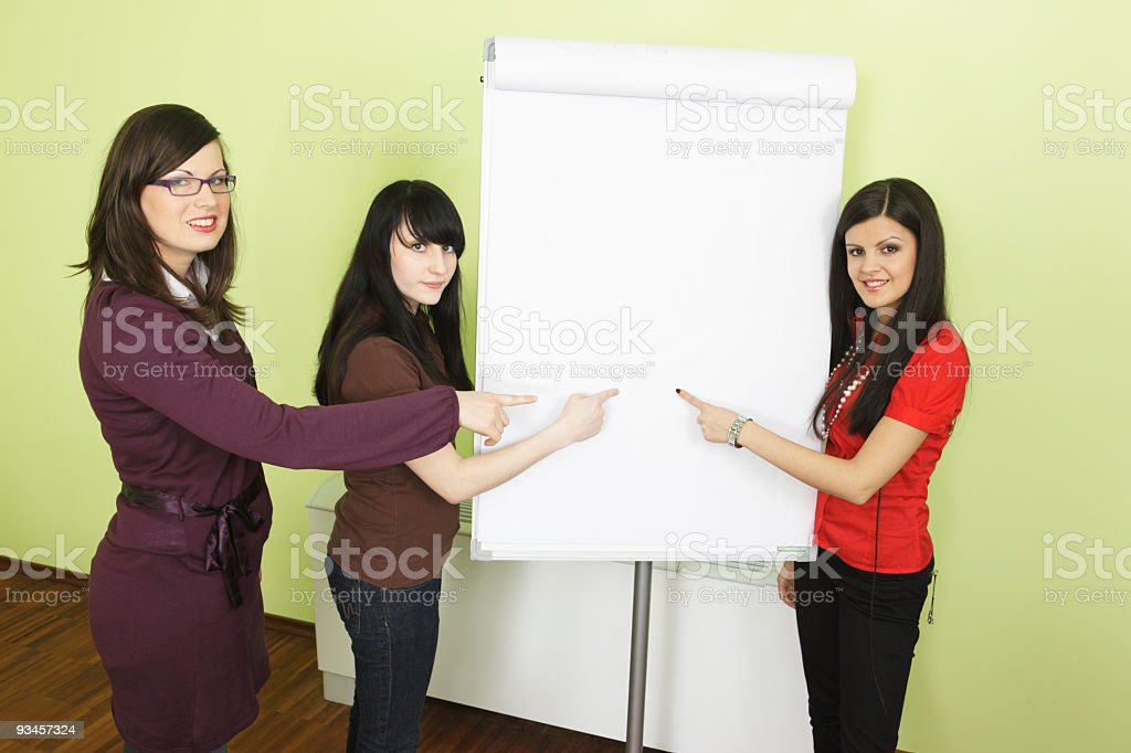 Three girls point to the blank chart wall royalty-free stock photo