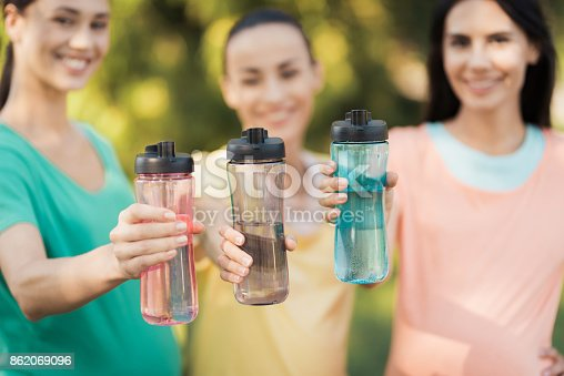 istock Three girls posing in the park putting forward their hands with sports bottles 862069096