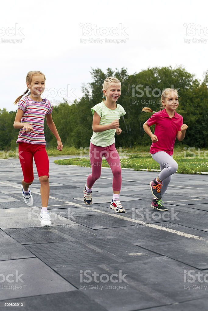 three  girls run down around the stadium stock photo