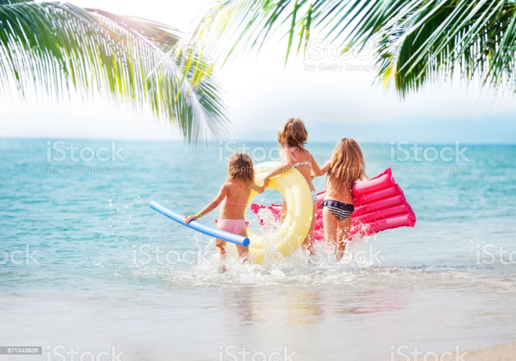 Three girls running in the sea at tropical beach stock photo
