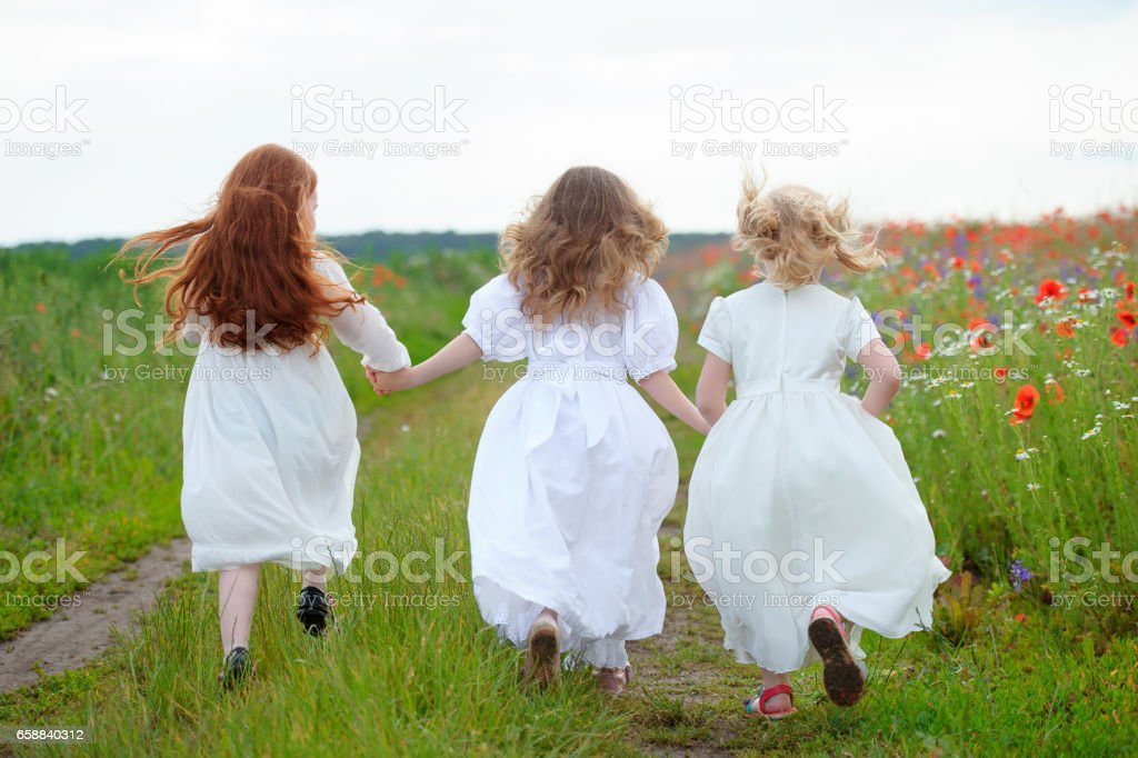 three girls running together joined hands stock photo