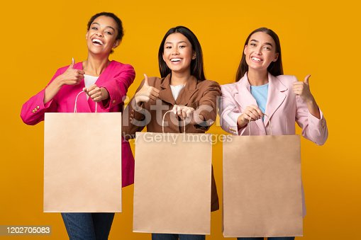 We Like Shopping. Three Girls Showing Blank Shopper Bags Gesturing Thumbs Up Posing In Studio On Yellow Background. Mockup