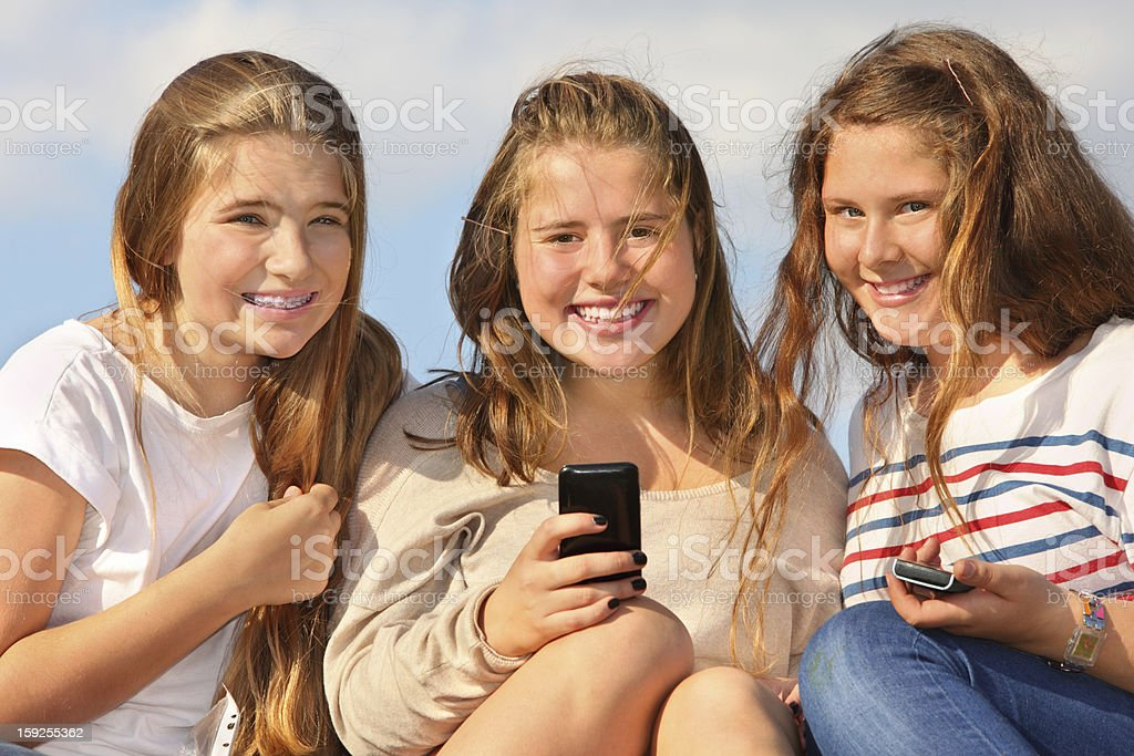 Three girls sit with mobile phones and smile stock photo