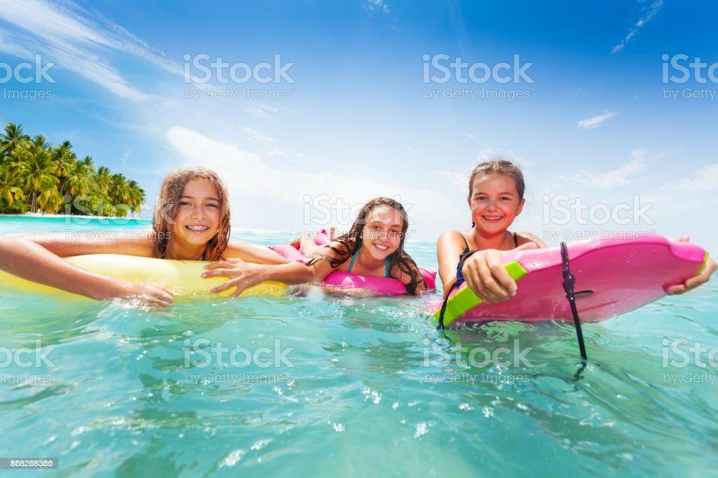 Três meninas nadam no mar em pranchas de surf - foto de acervo